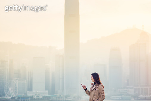 Busy businesswoman holding and using smartphone in modern city, with spectacular city skyline and compact highrise corporate buildings in the background. - gettyimageskorea