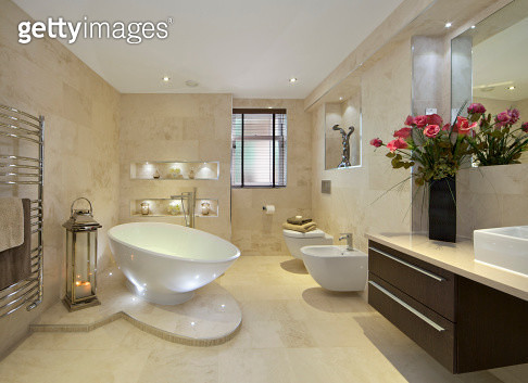 a modern bathroom in an expensive new home with a tear-drop shaped bath (full of water) sitting on a marble plinth. A bidet and WC are located near the window. A lantern with lit candles sits next to a large towel rail whilst a large bunch of red lilies s - gettyimageskorea