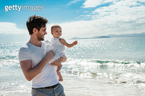 Spain, Lanzarote, father carrying his little daughter on the beach - gettyimageskorea