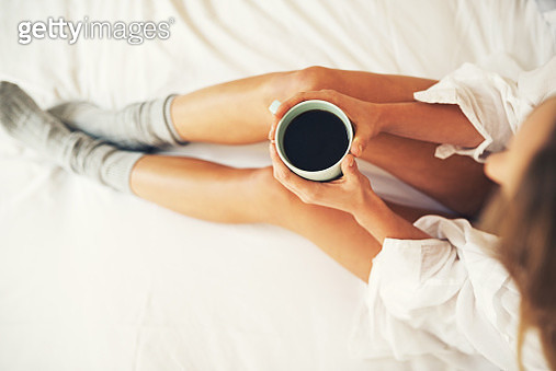 High angle shot of a relaxed young woman having coffee in her bedroom at home - gettyimageskorea