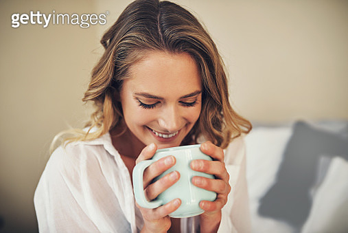 Shot of a relaxed young woman having coffee in her bedroom at home - gettyimageskorea