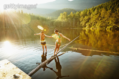 Couple balancing on logs in lake at sunset holding hands - gettyimageskorea