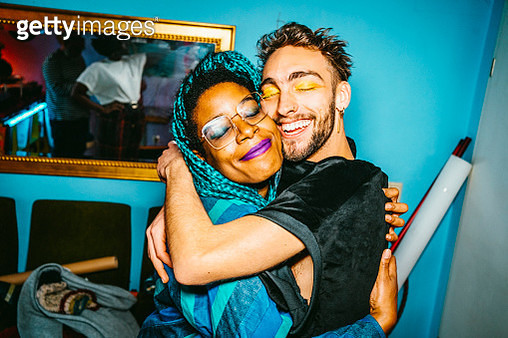 Happy male and female hipster friends hugging each other in living room - gettyimageskorea