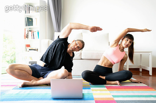 Man and woman in sports wear doing workout at home. Couple exercising together with watching laptop. - gettyimageskorea