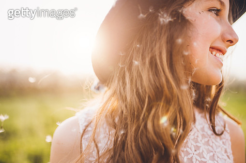 Young girl outside blowing dandelion-copy space - gettyimageskorea
