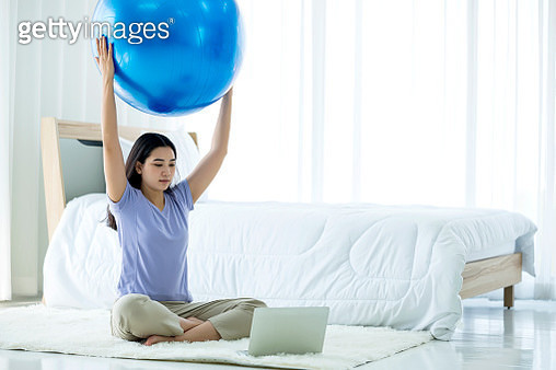 Young Asian woman doing gym ball yoga with laptop using Yoga application in bedroom. Healthy lifestyle at home. - gettyimageskorea