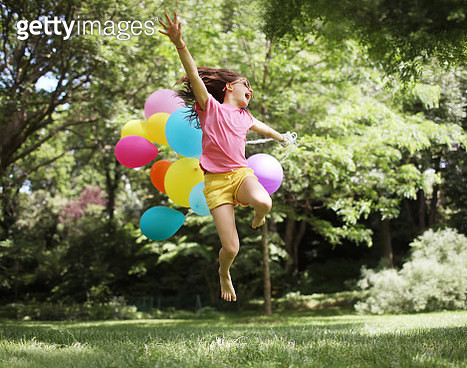 A 10 years old girl jumping with balloons in a park - gettyimageskorea