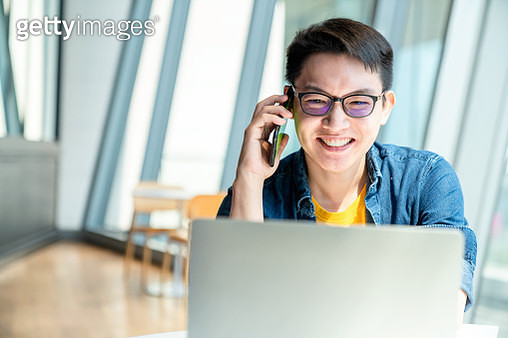 Small businessman working in office, doing a video call with laptop. Male professional working in office and making a video call. - gettyimageskorea