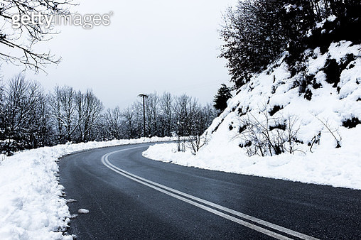 Winding road through snowy forest - gettyimageskorea