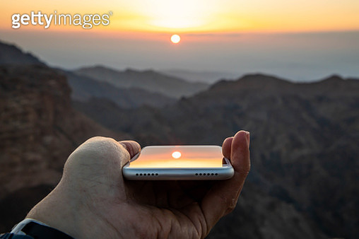Watching the sunset from Petra reflected in mobile phone. - gettyimageskorea