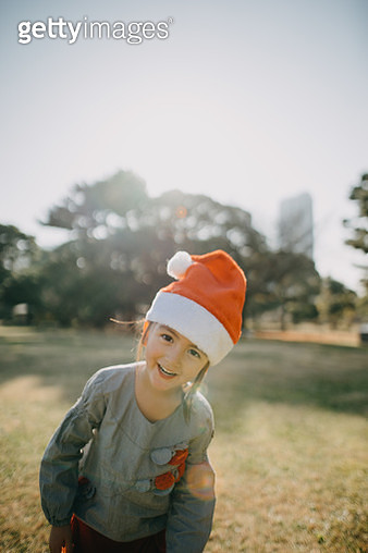 Cute mixed race girl wearing santa claus hat and smiling at camera - gettyimageskorea