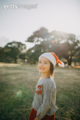 Cheerful mixed race little girl wearing santa claus hat - gettyimageskorea