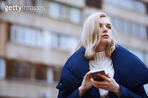 Young blond woman outdoors using smartphone in the city - gettyimageskorea