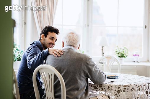 Happy caretaker communicating to senior man in nursing home - gettyimageskorea