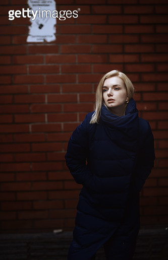 Young blond woman in blue down jacket standing next to the brick wall - gettyimageskorea