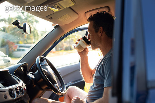Australian man starting his morning commute drinks his coffee out of a reusable coffee cup while sitting in his car in the morning sun. - gettyimageskorea