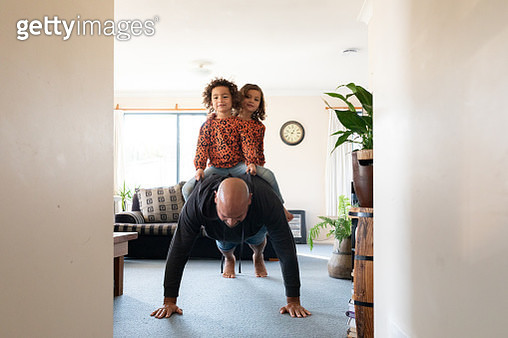 Dad doing push-ups with twin daughters on his back - gettyimageskorea