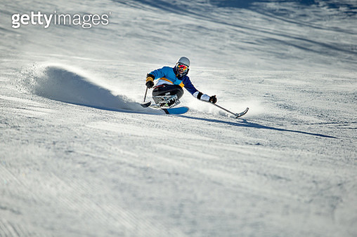 Guy with differing abilitie skiing down a ski run. - gettyimageskorea