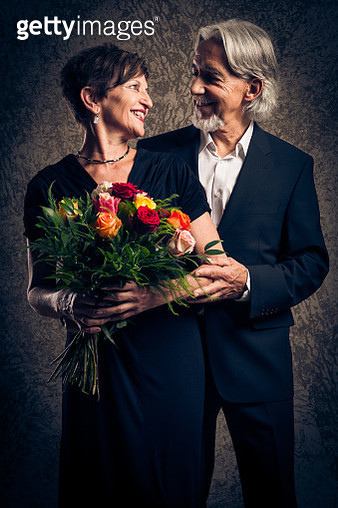 Happy Senior Couple Holding Bouquet Against Wall - gettyimageskorea