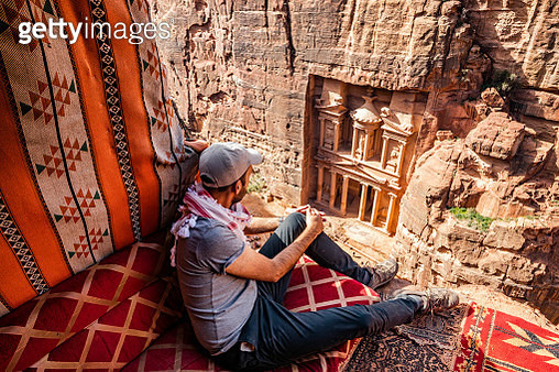 Guy in the perfect place to contemplate The Al-Khazneh Treasury tomb in the city of Petra from above. - gettyimageskorea