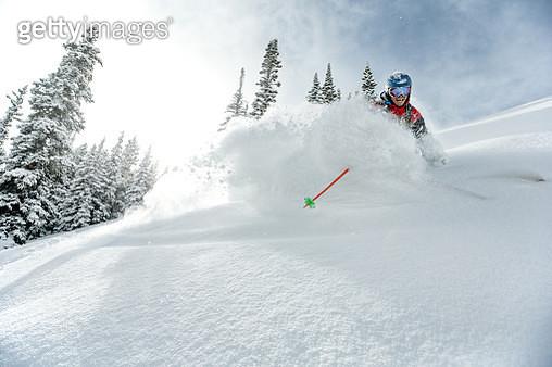 Skier making a powder turn on a sunny day. - gettyimageskorea