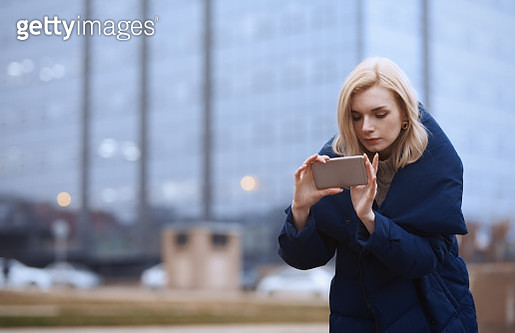 Young blond woman outdoors in the city making photo via smartphone - gettyimageskorea