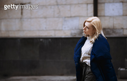 Young blond woman in blue down jacket waking in the city - gettyimageskorea