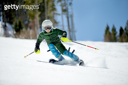 Young kid racing skis on a sunny day. - gettyimageskorea
