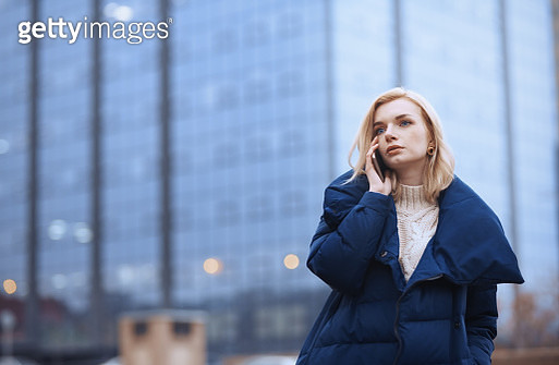 Young blond woman outdoors talking via smartphone in the city - gettyimageskorea