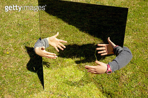 Creative picture of girl playing with mirror reflection in the backyard home. - gettyimageskorea