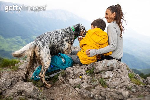 Mom and son stroking their dog in the mountains - gettyimageskorea