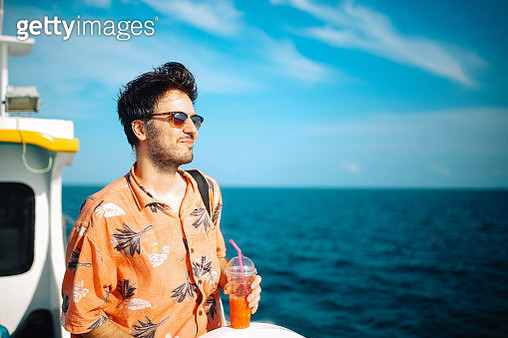 Young man relaxing on the boat while traveling in between Thai islands - gettyimageskorea