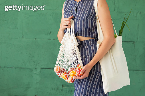 Female hands with shopping cotton mesh eco bag on green background. Zero waste concept - gettyimageskorea