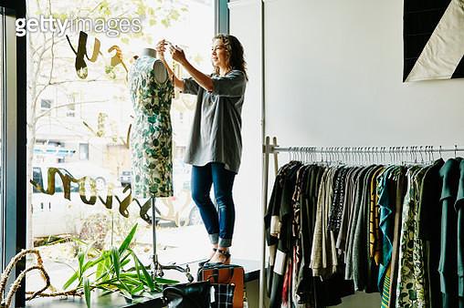 Female business owner dressing dress form - gettyimageskorea