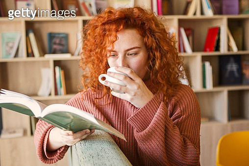 Woman sitting on sofa with mug of coffee in bookstore reading a book - gettyimageskorea