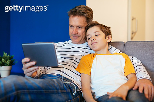 Father and son with earbuds and tablet on couch at home - gettyimageskorea