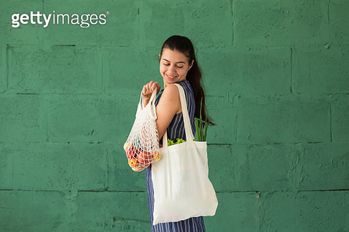 Woman shopping fruits and vegetables with reusable cotton Eco produce bag. Zero waste lifestyle concept - gettyimageskorea
