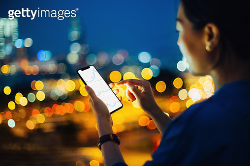 Businesswoman checking stock market data on mobile phone in city at night - gettyimageskorea