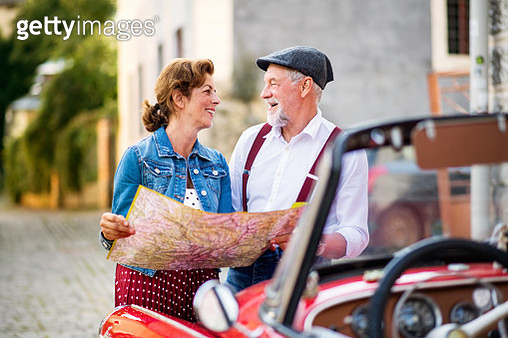 A portrait of happy man and woman standing by a convertible car, planning. - gettyimageskorea
