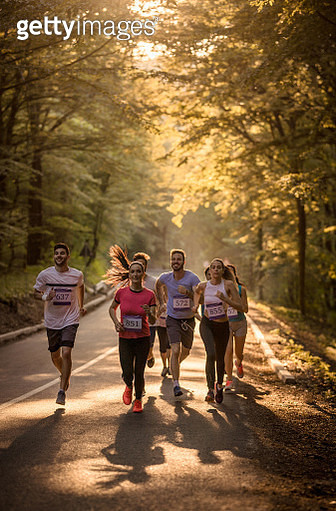Large group of athletic people running a marathon through the forest. - gettyimageskorea
