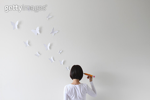 Rear view of woman holding pencil and imagining butterflies - gettyimageskorea