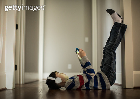 Young boy using digital tablet and headphones at home - gettyimageskorea
