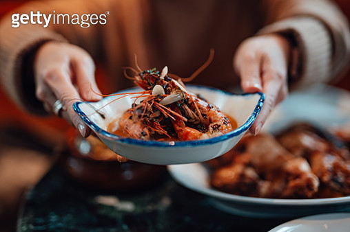 Young Woman Sharing Food With Friends At Restaurant - gettyimageskorea