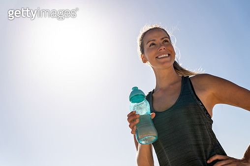 Athletic woman at the beach drinking water - gettyimageskorea