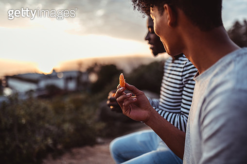 Friend sitting and sharing fruit - gettyimageskorea