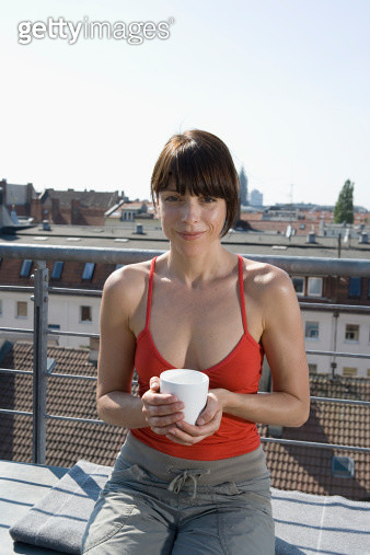 A woman sitting on a rooftop terrace with a cup of tea - gettyimageskorea