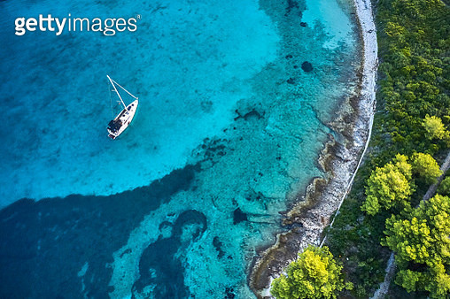 Anchored sailboat in shallow sea at island Veli Prznjak, Dalmatia, Croatia in autumn morning. High angle view photo from drone DJI Mavic 2 Pro (Hasselblad camera). - gettyimageskorea