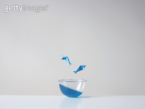 Conceptual fish jumping out of a glass bowl - gettyimageskorea
