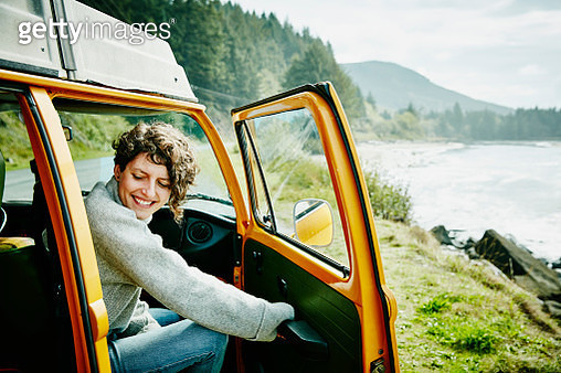 Smiling woman on road trip stepping out of van parked at ocean lookout - gettyimageskorea