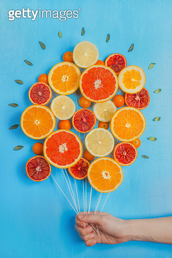 Bouquet of oranges and grapefruits, looking like a bunch of balloons. Sky-blue background. Greeting card. - gettyimageskorea
